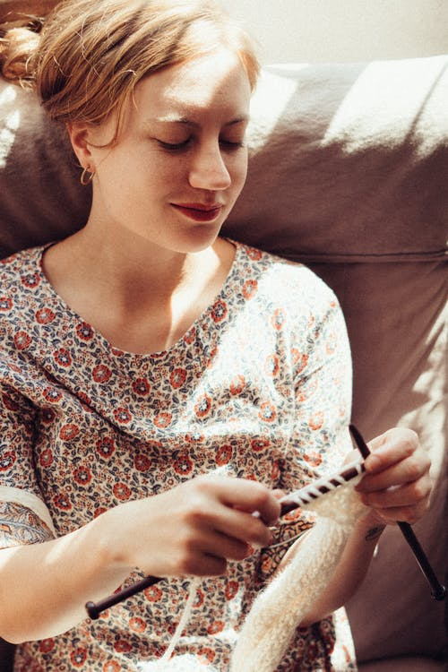 Woman in White Red and Blue Floral Shirt While Doing Crochet