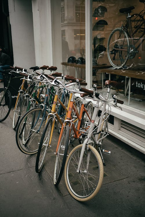White and Brown City Bikes Parked Beside Glass Window
