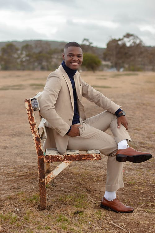 Photo of Man Wearing Formal Wear While Sitting on Bench