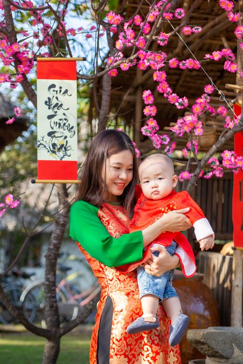 Woman in Red Long Sleeve Shirt Carrying Baby in Red and White Floral Dress