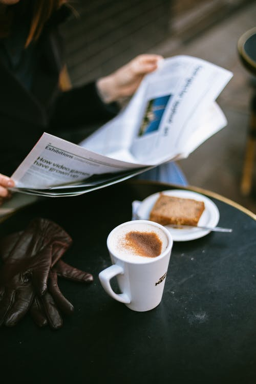 Person Having a Coffee and Reading a Newspaper
