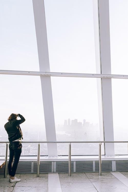 Man in Black Jacket Taking Photo Outside a Glass Window