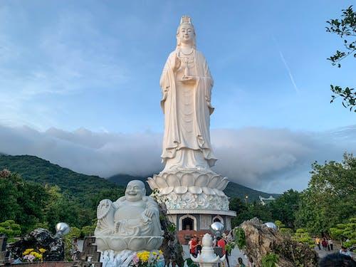 Lady Buddha statue against cloudy blue sky