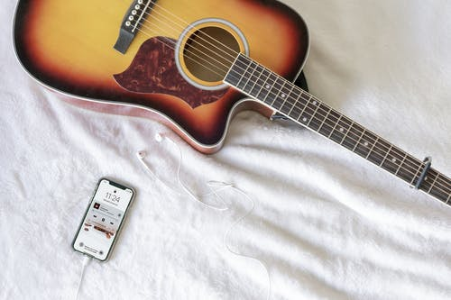 Red and Black Acoustic Guitar next to Smart Phone