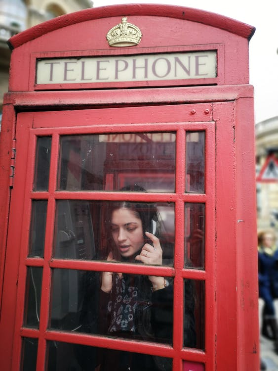 Woman in Black and White Floral Shirt Standing Inside Red Telephone Booth Making Call