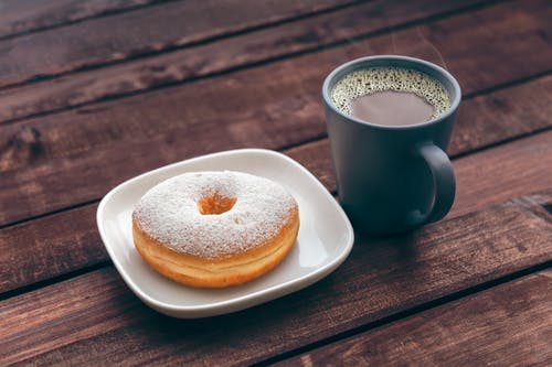 Doughnut On White Ceramic Plate Beside Ceramic Mug On Brown Wooden Table