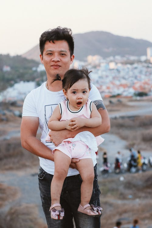 Man in White Crew Neck T-shirt Carrying A Baby Girl