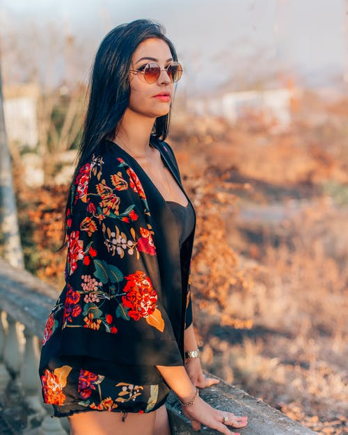 Woman in Black and Orange Floral Top Wearing Sunglasses