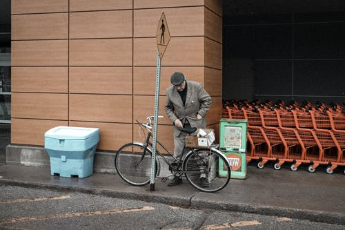 Man Parking a Bicycle Near Brown Wall