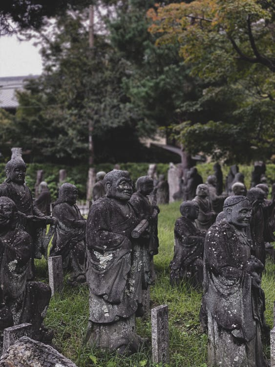 Old Buddhist sculptures near forest in park