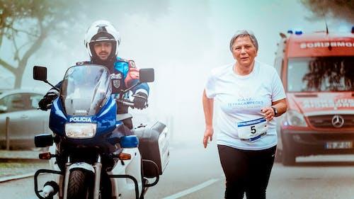 Homme En Moto Escorte Une Vieille Femme Avec Une Ambulance Rouge