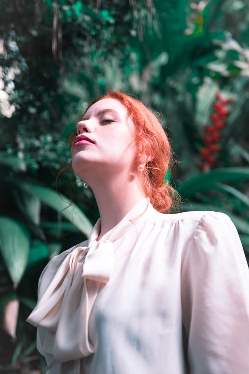 Selective Focus Photo of Woman with Red Hair Closing Her Eyes