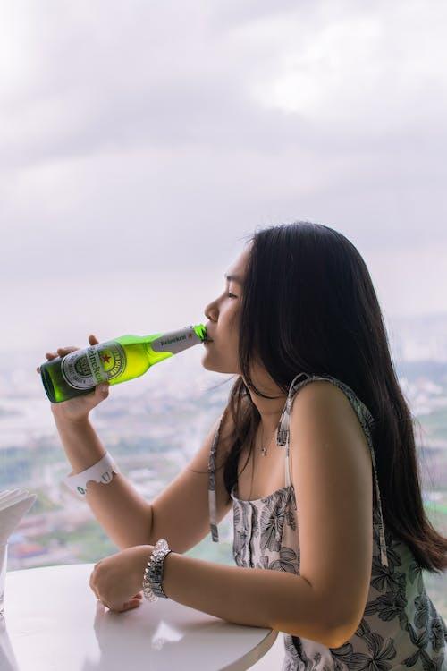 Wanita Minum Botol Kaca Hijau