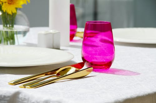 Purple Drinking Glass on White Table Cloth