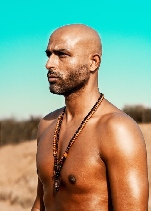 Topless Man Wearing Black and Brown Necklaces