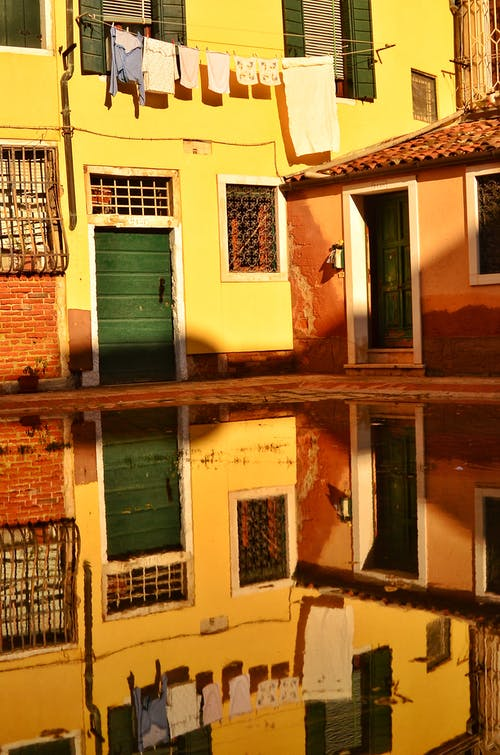 Bright yellow wall of old house and clothes on string reflecting in puddle