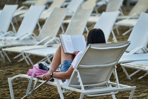 Woman in Blue Denim Shorts Sitting on White Folding Chair Reading Book