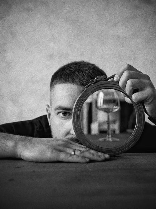Grayscale Photo of Man Holding Round Mirror
