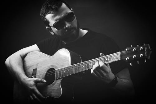 Gray scale of Man in Black Sunglasses Playing Acoustic Guitar