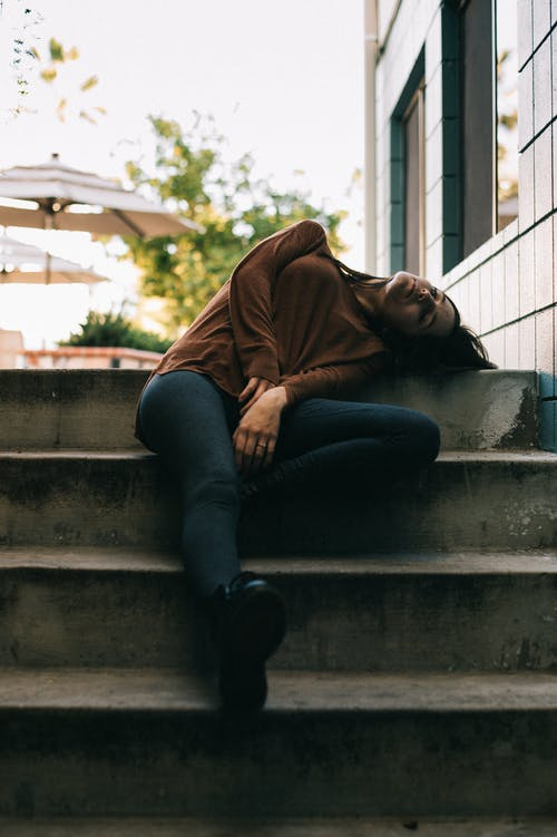 Woman in Brown Long Sleeved Top and Black Pants Sitting While Sleeping on Gray Concrete Stairs