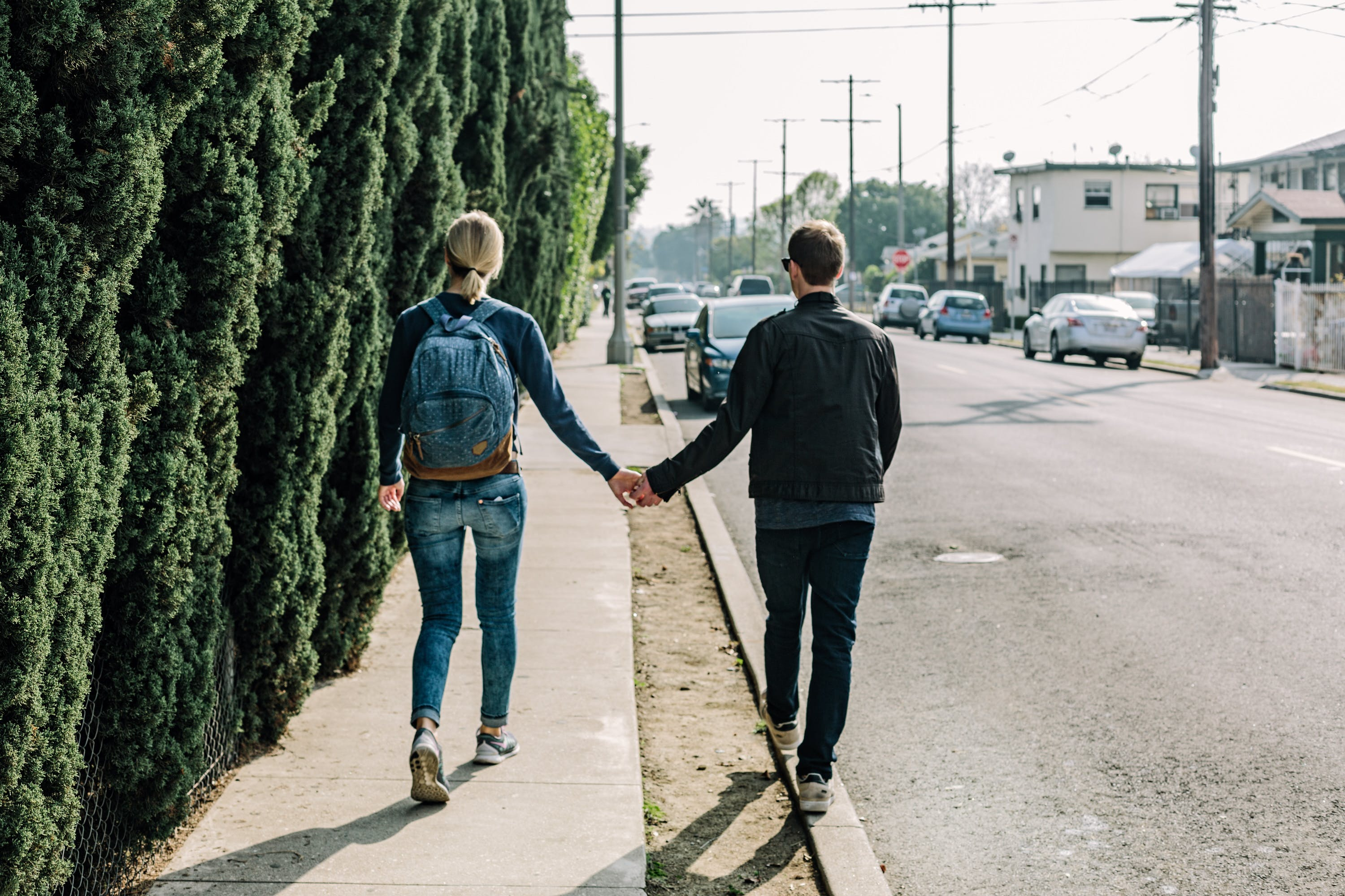 Man Holding Woman While Walking on Sidewalk