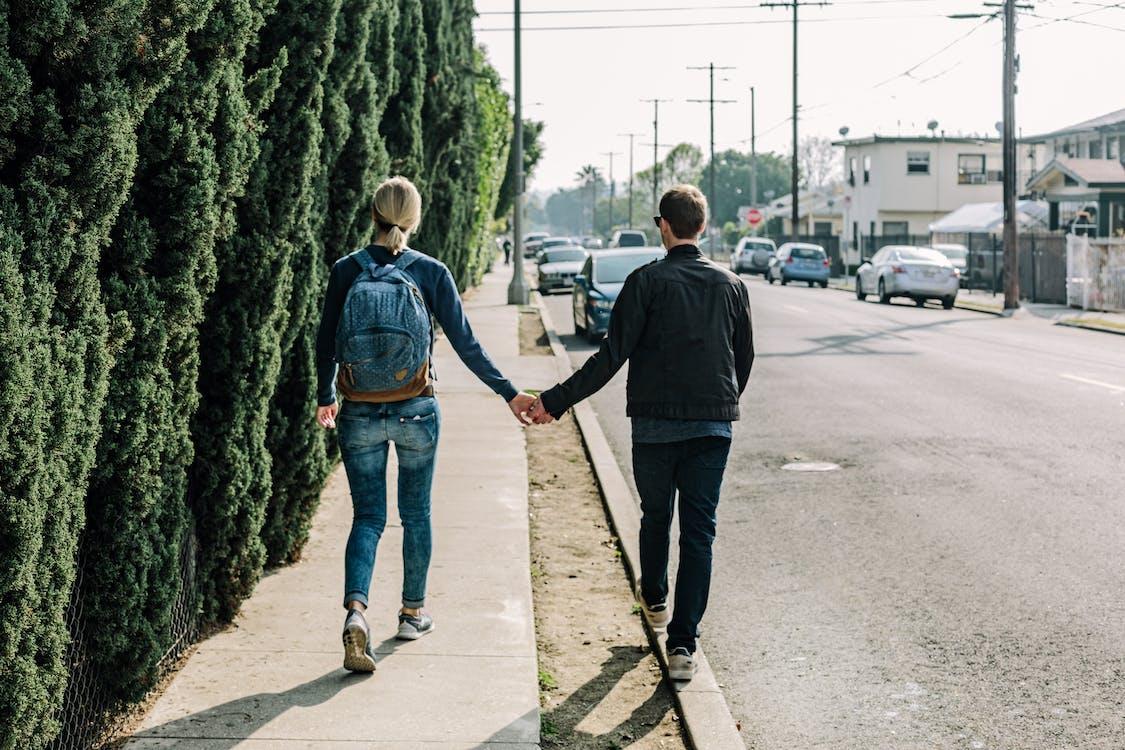 Man Holding Woman While Walking on Sidewalk