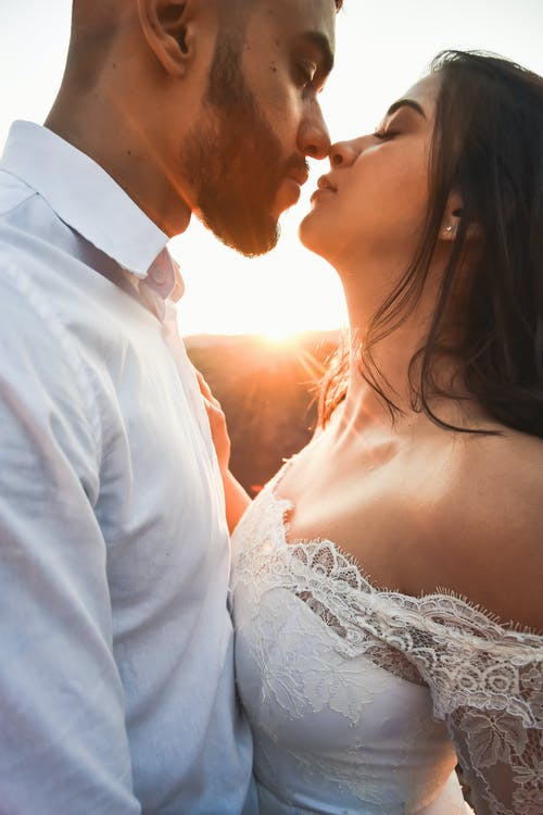Man in White Dress Shirt Kissing Woman in White Wedding Dress