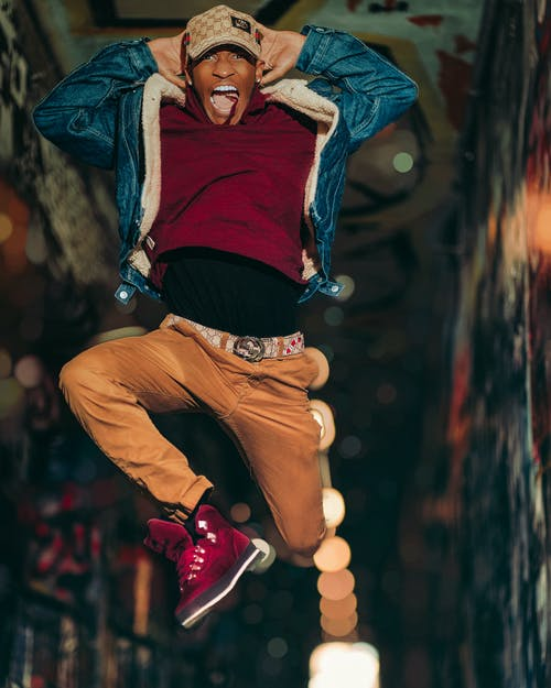 Man in Red Shirt and Brown Pants Wearing Red Sneakers Jumping