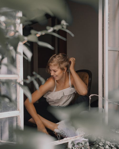 Woman Wearing White Top Sitting by the Window