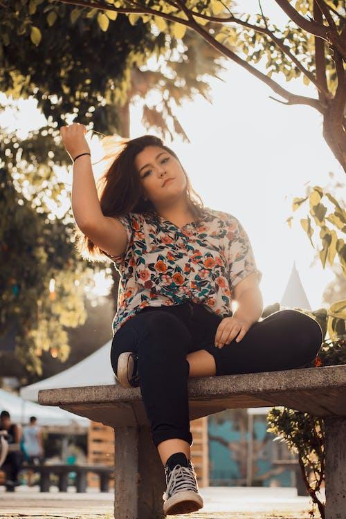 Женщина в рубашке с цветочным рисунком и черных джинсовых джинсах, сидя на скамейке
