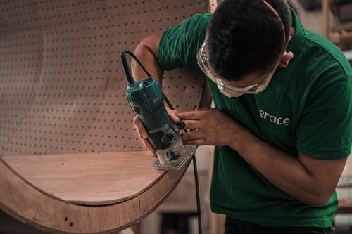Man in Green T-shirt Using Router on Wooden Piece
