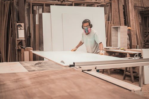 Man Working on a Wooden Board
