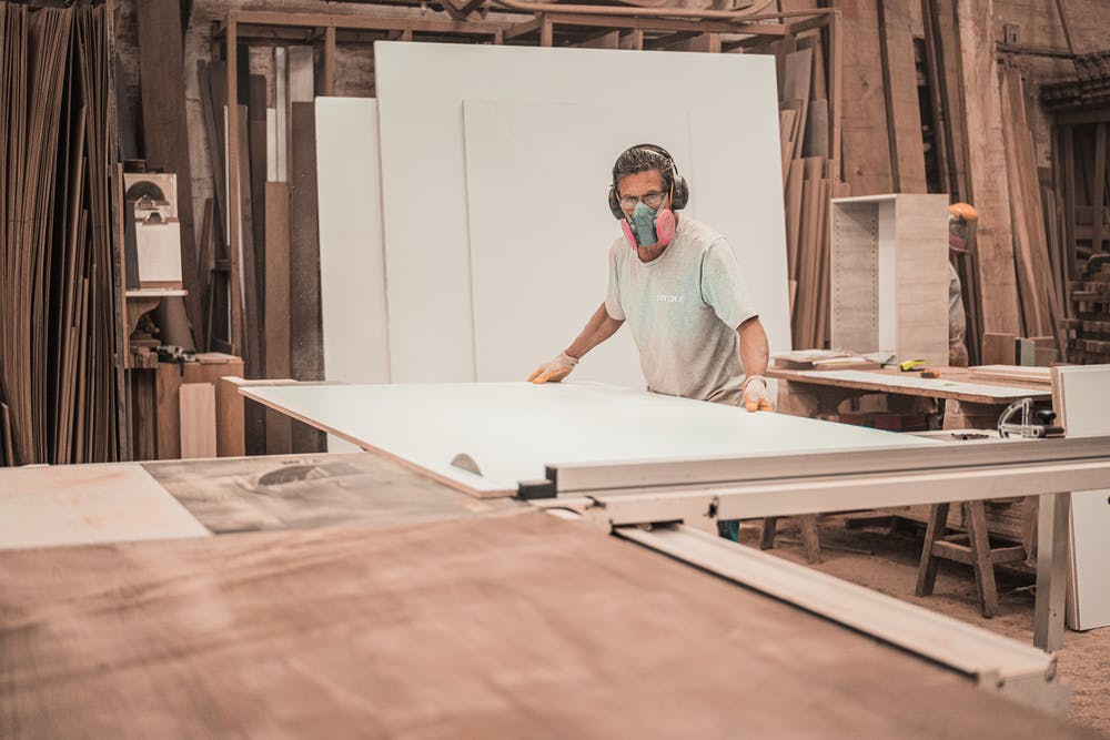 Man working on a wooden board.   Photo: Pexels