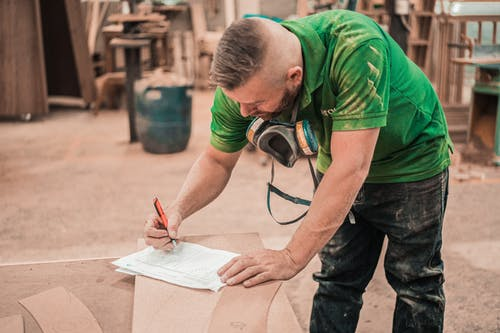 Man in Green T-shirt Writing on White Paper