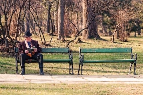 Man Sitting on Green Bench