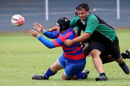 Men Playing Football On Green Grass Field