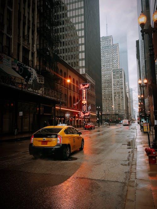 高層建築之間的道路上的黃色出租車