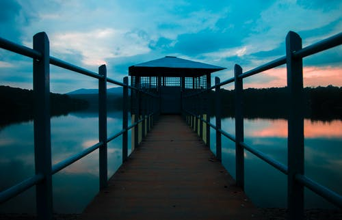 Brown Wooden Dock on Body of Water Under Cloudy Sky