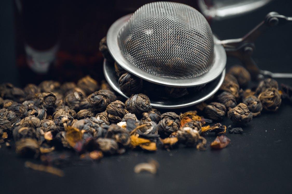 fresh brown coffee beans in metal strainer