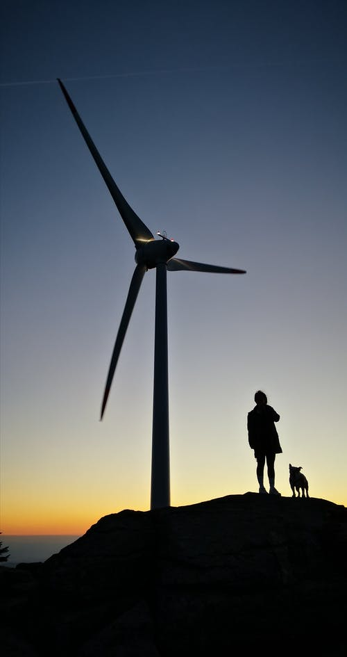 Silhouette Of Person Standing Near Windmill