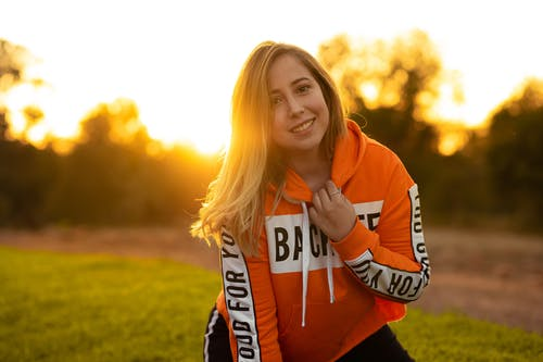 Woman in Orange and White Hoodie Smiling