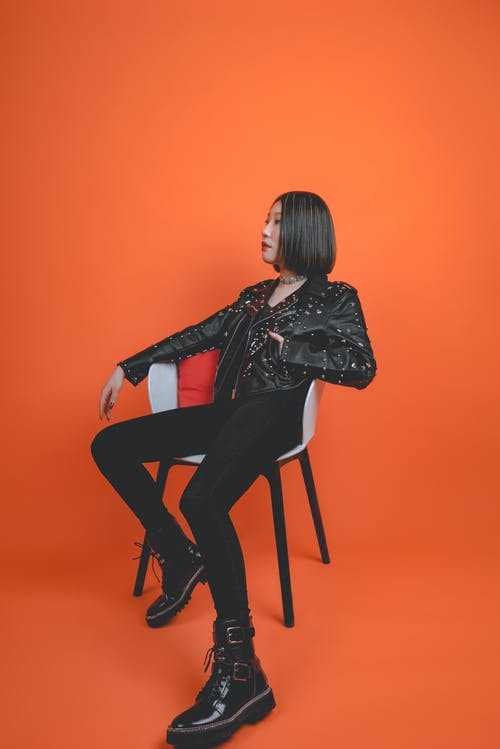 Woman In Black Leather Jacket And Black Pants Sitting On Chair