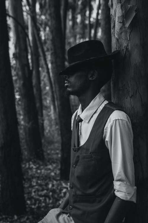 Grayscale Photo of Man Wearing Hat and Vest Leaning on Tree