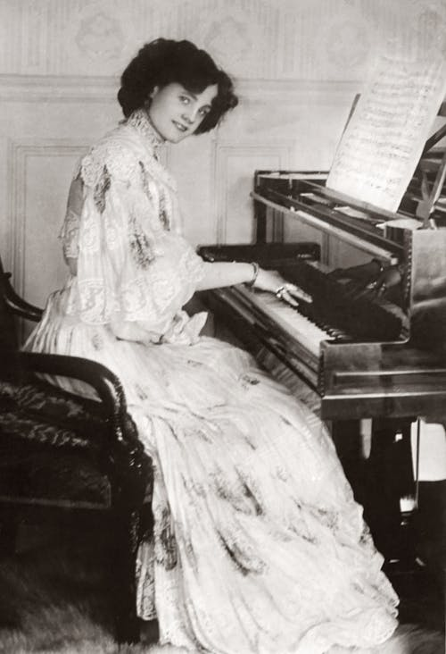 Woman in White Dress Playing the Piano