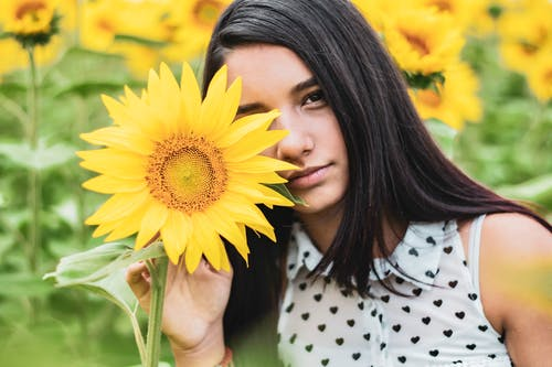 Woman In White And Black Polka Dot Shirt Holding Sunflower