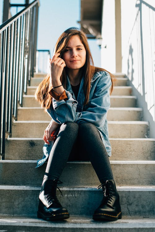 Woman In Blue Denim Jacket And Black Pants Sitting On Stairs