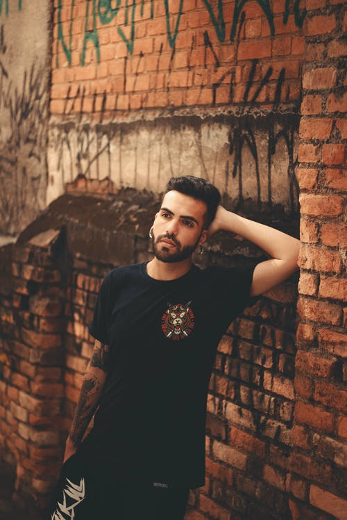 Man In Black Crew Neck T-shirt Standing Beside Brick Wall