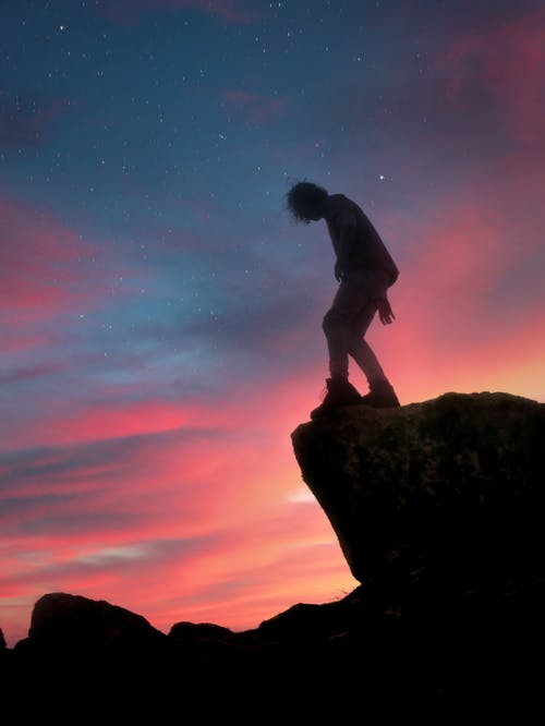 Silhouette of Man on the Edge of a Rock during Night Time