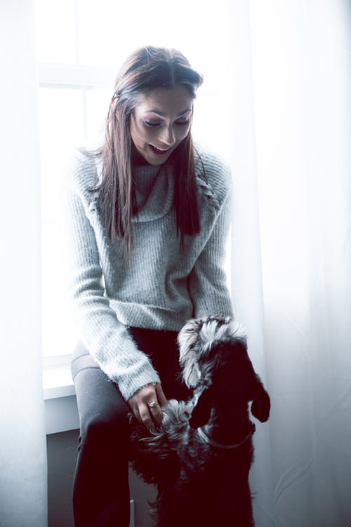 Woman in Gray Sweater with a black dog