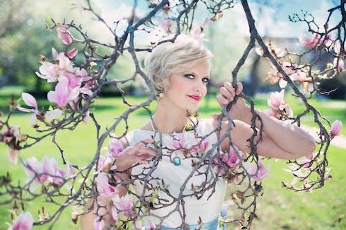 Blonde Frau, Die Auf Blattlosem Rosa Blühendem Baum Aufwirft